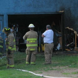 Deputy Chief Chris Bryant of the Rumford Fire Department, center left, and Al White, a tenant at 1806 Route 2 in Rumford, talk outside a garage that caught fire late Saturday afternoon when flames engulfed a riding lawnmower parked beside the garage.