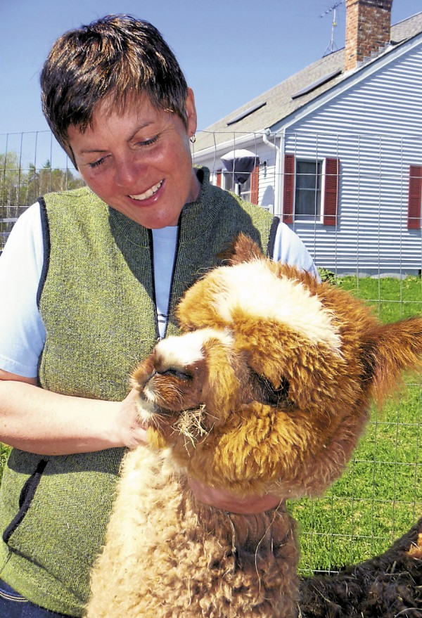 Robin Fowler of Northern Solstice Alpaca Farm in Unity cuddles with Riata at the farm.