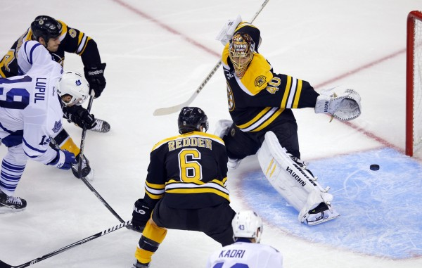 Toronto Maple Leafs left wing Joffrey Lupul (left) scores a goal against Boston Bruins goaltender Tuukka Rask, and between Boston Bruins defensemen Adam McQuaid (top left) and Wade Redden, in the second period of Game 2 of their NHL Eastern Conference Quarterfinal hockey playoff series in Boston Saturday night.