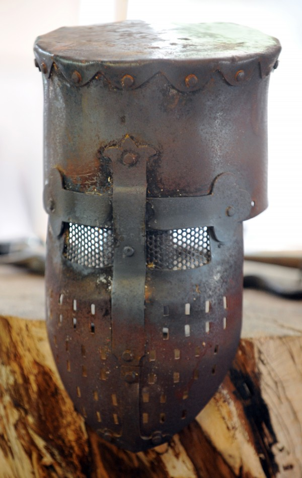 A metal helmet made by Matt Johnston awaits being made into a cooking pot in Johnston's workshop. Johnston creates his own metal armor and helemts for use at the SCA events he attends. His plans to make the helmet into a cooking pot mimic what might have been done with a old helmet in medieval times.