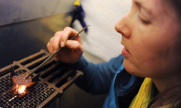 Karen Childs of Bangor checks the arrangement of copper pieces as the first layer of powdered glass melts to form a seal on the copper brooch she is creating. Childs is using copper and glass, items that would commonly be used to create similar jewelry in medieval times.