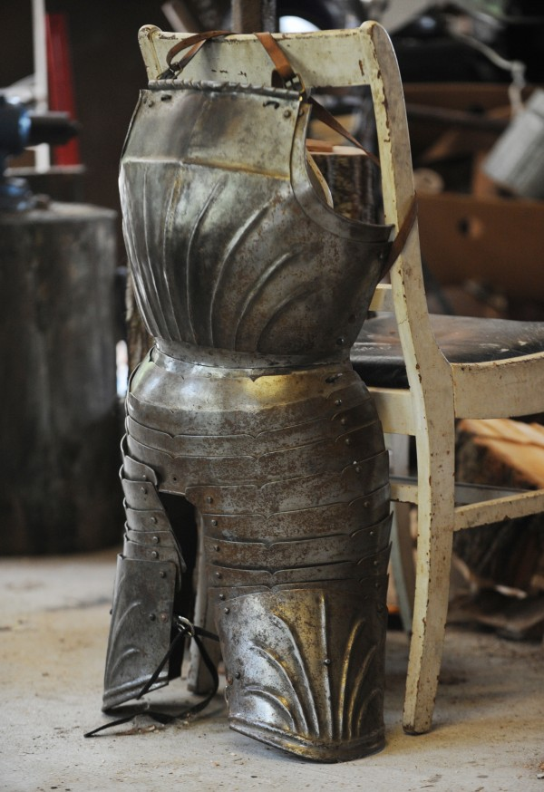 Metal armor hangs on the back of a chair in Matt  Johnston's Dedham workshop. Johnston is an active member of the SCA and makes his own metal helmets and armor to match his 1520s Bavarian outfit.