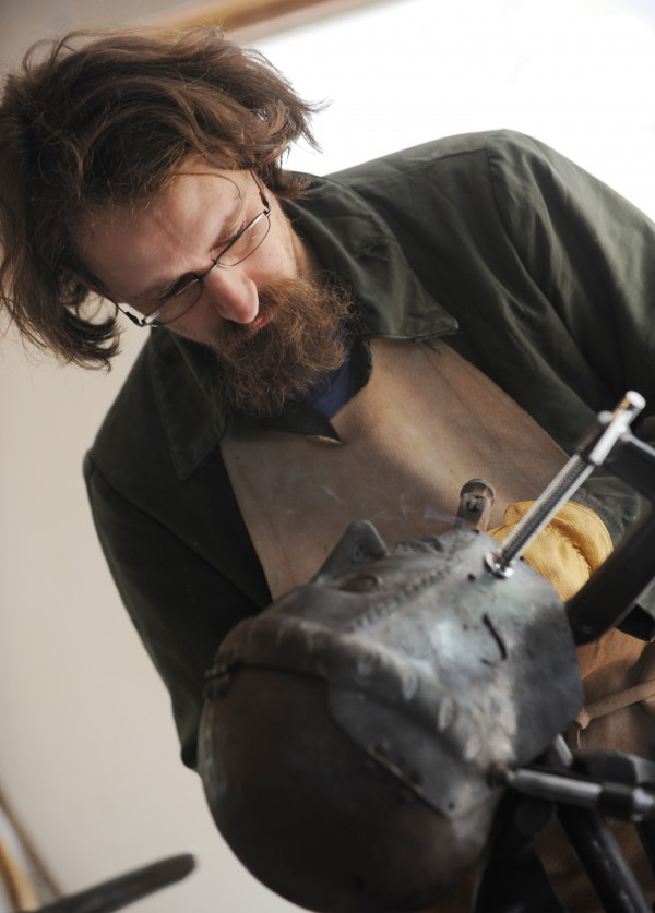 Matt Johnston uses a torch to heat the metal on his fencing helmet to cherry-red before taking a hammer to it to adjust the way it closes. Johnston made the helmet as part of his 1520s Bavarian SCA outfit.