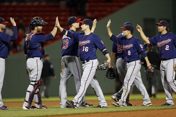 Minnesota Twins catcher Ryan Doumit (9) celebrates with left fielder Josh Willingham (16), shortstop Jamey Carroll (8) and second baseman Brian Dozier (2) after defeating the Boston Red Sox 6-1 Tuesday night at Fenway Park in Boston.