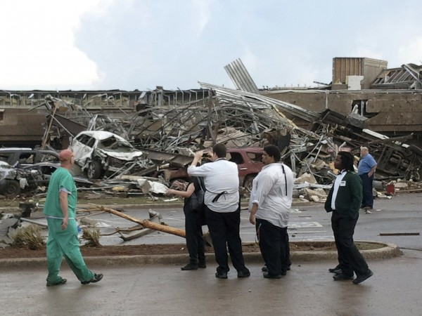 People look at the destruction after a huge tornado struck Moore, Oklahoma May 20, 2013. A huge tornado with winds of up to 200 miles per hour devastated the Oklahoma City suburb of Moore on Monday, ripping up at least two elementary schools and a hospital and leaving a wake of tangled wreckage.