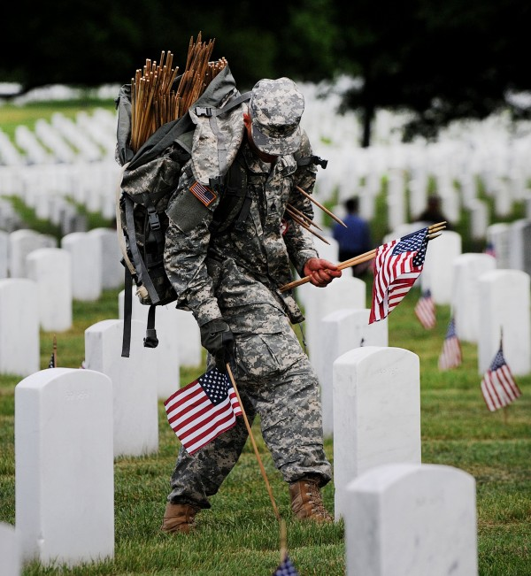 Soldiers in the Third U.S. Infantry Regiment (The Old Guard) place a small American flag one foot in front and centered before each grave marker for more than 220,000 graves during the annual Flags-In ceremony in advance of Memorial Day to honor the nation's fallen members of the military May 23, 2013 in Arlington Cemetery, Virginia.