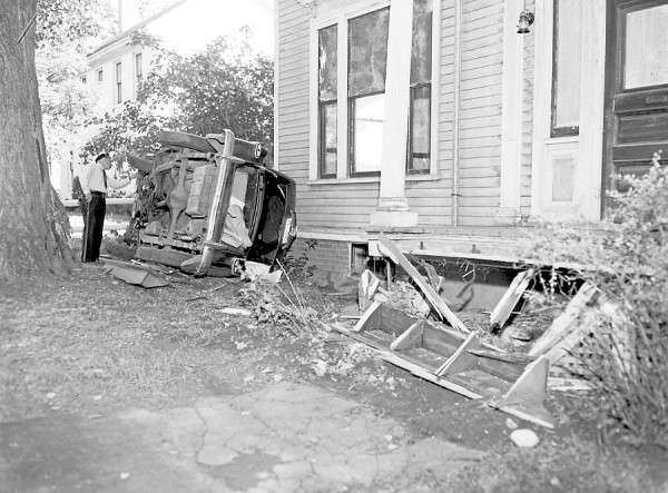 Startled by a spider, of which she admitted being &quotdeathly afraid,&quot Olive A. Hall, 46, of bangor, lost control of her automobile on Monday morning, July 2, 1951, and the vehicle ripped the front steps off an Ohio street house and then rolled over on its side. Hall told police that the spider appeared on the car window and the vehicle went out of control as she tried to close the window. The car went across the sidewalk and tore off the steps of the residence at 247 Ohio street, owned by A.L. Strout of Old Town. The vehicle then grazed a tree and tipped over. The driver escaped injury. Patrolman Clifton E. Slean is seen in the picture examining the badly damaged car.