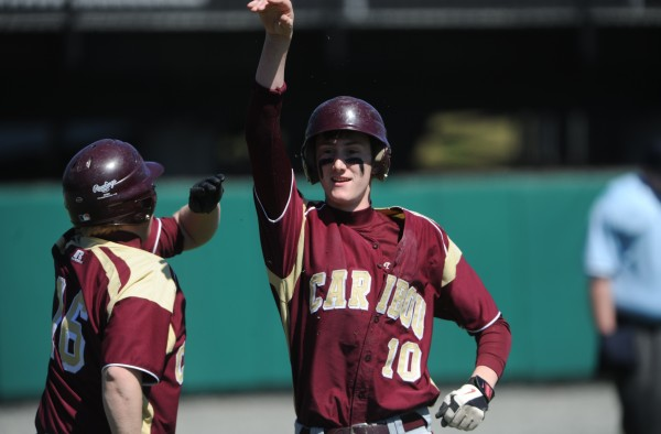 Caribou's Cody Herbert, right, gets a high five from his teammate Matt Manter after scoring a run against John Bapst during the third inning of game one of a doubleheader at Husson University in Bangor on Friday. John Bapst won 3-2.