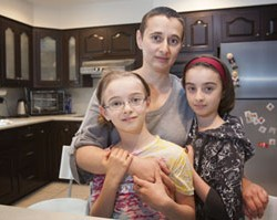 Maria Brodsky and her two daughters Sarah, 9, left, and Rachel 10, right, in the kitchen of their Huntington Valley home. Maria has had issues with medical costs on both of the girls; Sarah needed an MRI two years ago to examine a tumor in her head, Rachel needed lab work for a knee injury. Prices for the procedures varied greatly between providers.