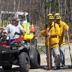 Firefighters confer near the scene of a 10-acre woods fire off Perkins Valley Road in Woodstock on Wednesday afternoon.