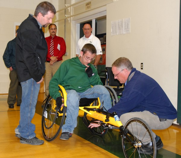 Fort Kent Community High School track team member Robbie Hebert is helped into his new racing wheelchair by friends and family Friday afternoon. The chair was presented to Hebert during an impromptu ceremony Friday afternoon.