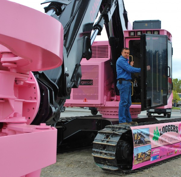 Dustin Marquis at the door of his Tigercat feller buncher timber harvester which he painted bright pink as part of Loggers for Cancer's efforts to raise awareness and funds for cancer research and victims.
