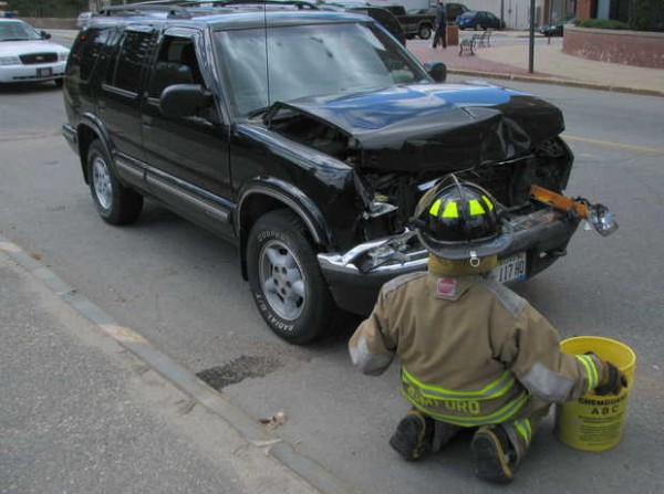 Rumford firefighter Jeff Harren waits to throw more absorbent material onto fluids leaking from a Chevrolet Blazer involved in a three-vehicle collision on Route 108 in downtown Rumford on Friday.