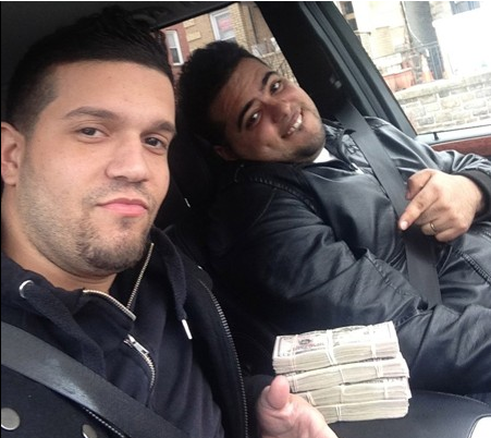 In this undated photo released by the U.S. Attorney's Office for the Southern District of New York, Elvis Rafael Rodriguez, left, and Emir Yasser Yaje pose with bundles of cash allegedly stolen using bogus magnetic swipe cards.
