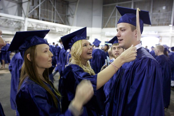 From left, University of Maine, Orono business majors Casey Hudson and Brooke Matheiu try to fix Nick Roux's tassel before they attend the 2013 graduation ceremony at Alfond Arena Saturday, May 11 2013.