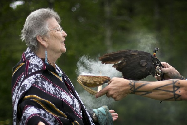 Sage smoke is fanned over Rose Sirois, of South Portland, during a smudging ceremony at the Metis of Maine annual pow-wow, Saturday, June 8, 2013, in Dayton. Smudging is a way to cleanse negative energies, spirits or influences.