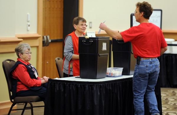 A voter casts his ballot at the Cross Insurance Center in Bangor on Tuesday.