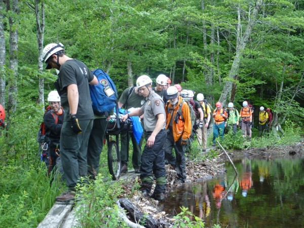Acadia National Park rangers and members of Mount Desert Island Search & Rescue carry a Brownville man down Canon Brook Trail after the man slipped and fell 40 feet over a waterfall while hiking on the trail on Saturday.