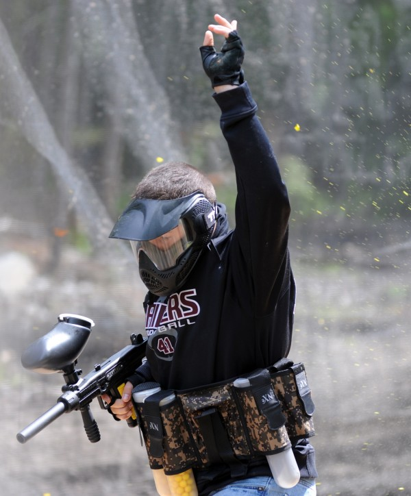 Kade Feeney raises his hand to signal he is out of the game after being shot by an opponent at the new paintball course at Maine Military Supply in Holden.