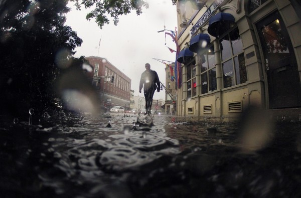 A pedestrian walks through West Market Square during a downpour on Friday.