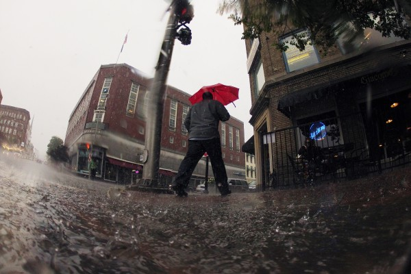 A pedestrian walks crosses Hammond Street during a downpour on Friday.