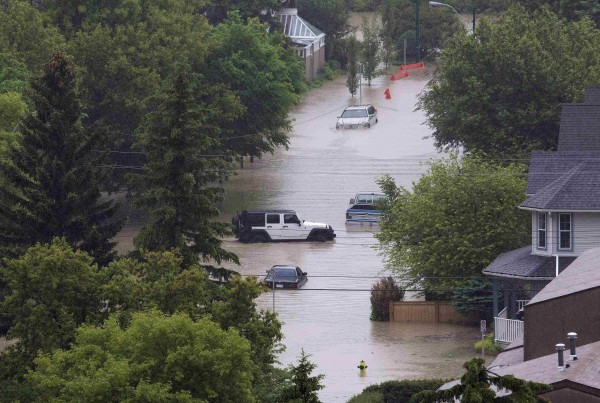 Vehicles surrounded by floodwaters are seen in the neighborhood of Sunnyside in Calgary, Alberta on Friday. Around 100,000 people of Calgary's 1.1 million residents, were ordered to leave their homes, while smaller communities were evacuated elsewhere in the Western Canadian province.