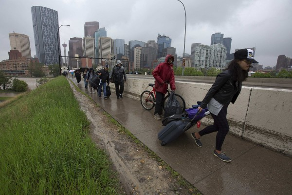 Residents leave the flooding downtown core as new orders evacuating all of downtown were issued in Calgary, Alberta on Friday. Many communities across southern Alberta are on mandatory evacuation orders because of severe flooding.