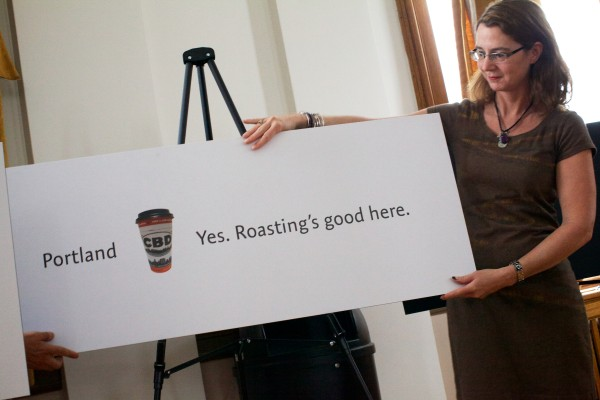 Maryallen Lindeman of Coffee By Design unveils a variation on Portland's new branding campaign at city hall Tuesday.