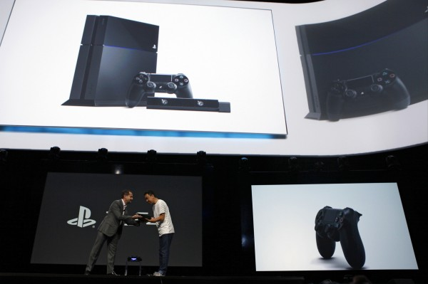 Andrew House (left), president and group CEO of Sony Computer Entertainment, passes the company's PlayStation 4 console on Monday to a designer during Monday's media event in Los Angeles. Sony unveiled PlayStation 4, its first new console in seven years.