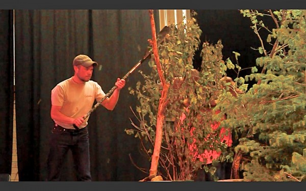 Chris Young of Greenville demonstrates how to create the sound of a bull thrashing through bushes with a canoe paddle during the 2013 Maine Moose Calling Championship in Greenville on June 15. Young won the competition.