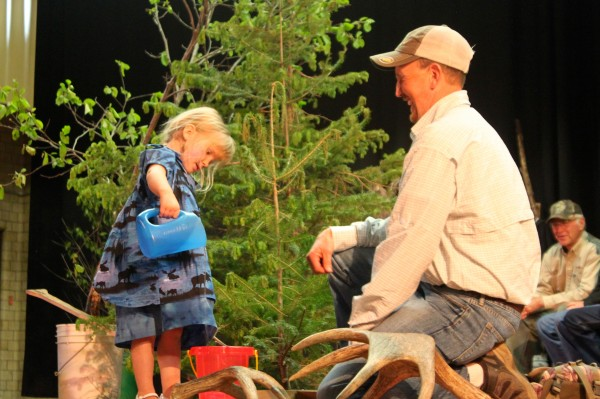Laureli Winslow, 3, of Washington pours water into a bucket to mimic the sound of a moose peeing in a bog or lifting its head out of the water during the 2013 Maine Moose Calling Championship in Greenville on June 15. She was the youngest competitor in the championship by far.