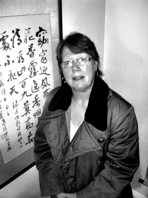 Sandra Hutchison wears a style of coat popular in China when she lived there 24 years ago, standing in front of calligraphy given to her by students.