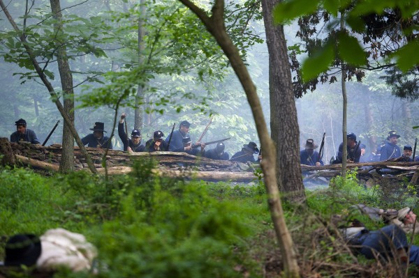 Actors playing Confederate troops charge up a hill towards Union forces during a reenactment of The Battle of Little Roundtop during the Blue Gray Alliance events marking the 150th anniversary of the Battle of Gettysburg, in Gettysburg, Pennsylvania June 30, 2013.