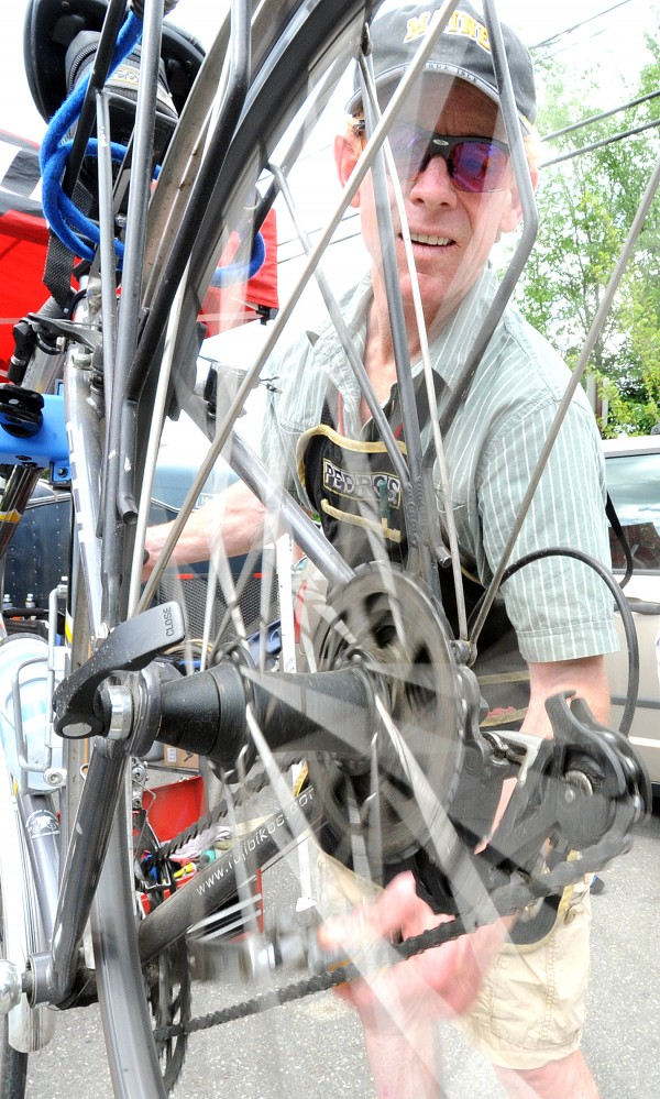 Stephen Higgins of Presque Isle adjusts a bike in the parking lot of the student center at the University of Maine at Farmington during the opening day of the 2013 Trek Across Maine. Higgins volunteered at one of several bike repair stations set up along the route and at the start and finish lines.