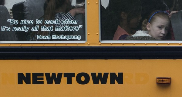 Students sit behind a quote by slain Sandy Hook Elementary School principal Dawn Hochsprung, displayed on the window of a school bus, as it approaches a stop near the original site of Sandy Hook Elementary School in Newtown, Connecticut June 14, 2013. Six months after a gunman massacred 26 children and adults at the elementary school, Newtown, Connecticut, marked the day with 26 seconds of silence and an expression of frustration at the stalled progress on gun control.