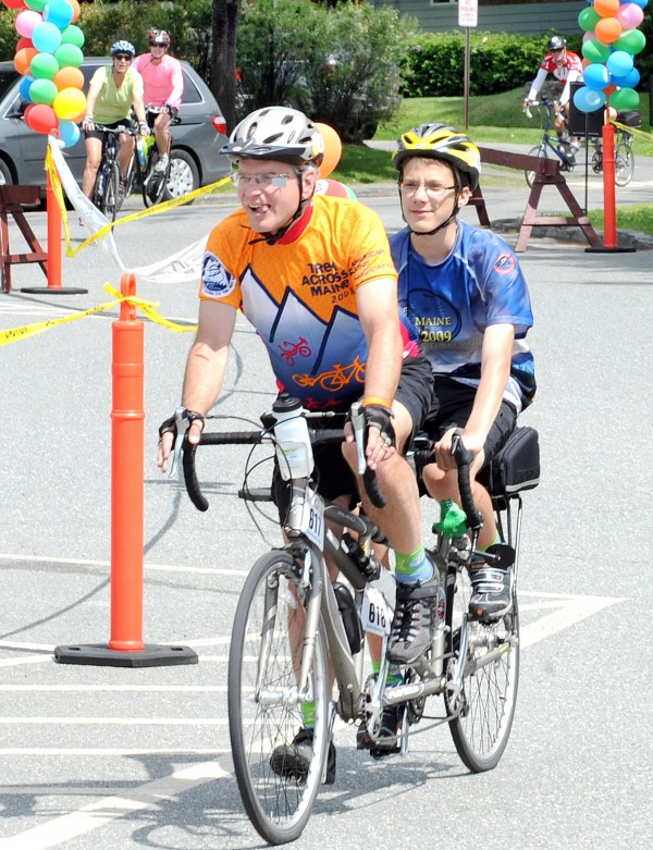 Bruce Hall and his son, Eric, of Lewiston cruise through the parking lot at the University of Maine at Farmington on Friday afternoon after crossing the finish line on the first day of the Trek Across Maine. The 180-mile ride is the largest American Lung Association cycling event in the country.
