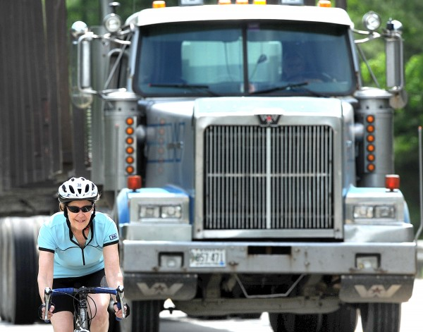A participant in the 2013 Trek Across Maine coasts down Route 2 in Wilton as a tractor-trailer approaches Friday.