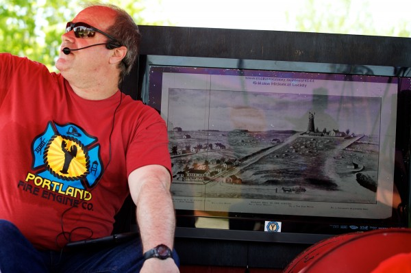 Tim Lambert points out the Portland Observatory on Munjoy Hill Friday while showing tourists, aboard a 1971 fire truck, a photo of what the hill looked like more than a hundred years ago. Lambert works for the Portland Fire Engine Co.