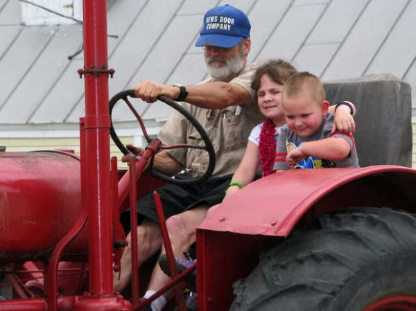 Jack Dews and his grandchildren, Oliver (right), 3, and Eva, 5, of Cumberland, wait atop Jack's 1932 McCormick-Deering 10-20 tractor early Saturday afternoon during a single-file parade through the pulling ring building during the 18th annual Maine Antique Tractor Festival at the Farmington Fairgrounds. Dews said that the tractor seat they're all sitting in came out of a school bus that once held 66 children and one bus driver.