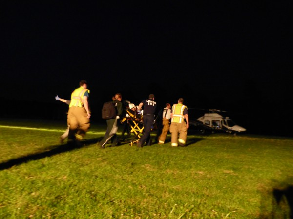 Bowdoin, Bowdoinham and Lisbon fire and rescue crews help LifeFlight paramedics load a motorcycle crash patient into a helicopter bound for Central Maine Medical Center Saturday night at Bowdoin Central School.