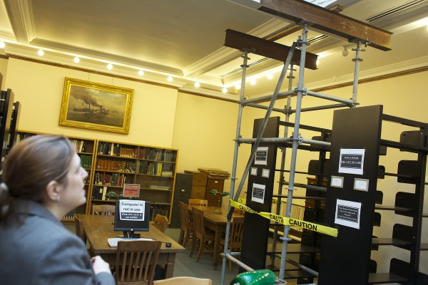 From left, Kate Villa, the campaign director for the Bangor Public Library, looks over at scaffolding that is holding up a cracked beam inside the Bangor Public Library Friday morning in Bangor. The library needs $3 million for a new roof among other repairs.