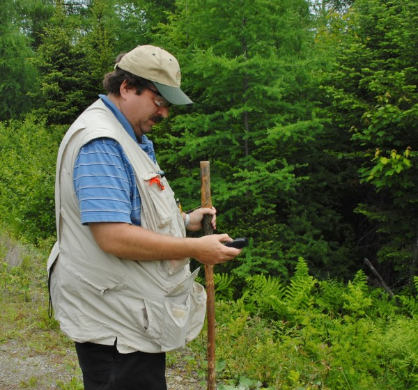 Aviation history buff Peter Noddin consults his GPS before striking out into the Maine woods in search of a 1960s-era military plane crash site.