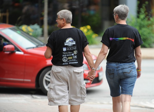 Diane Winnie Winter of Old Town, left, and Carroll Mann of Concord N.H. hold hands as they walk through the Bangor Price festival on Saturday in West Market Square. The two women met for the first time this weekend after finding each other online.