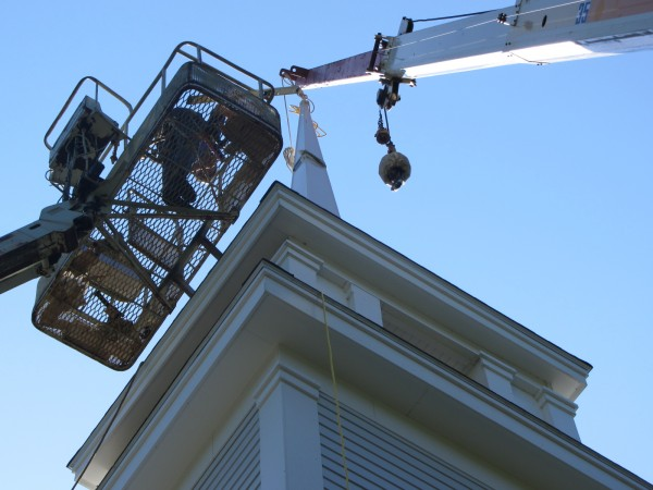 A worker from Frost & Bryant is high above the Rockville Community Chapel Wednesday morning to erect a steeple to the 162-year-old building.