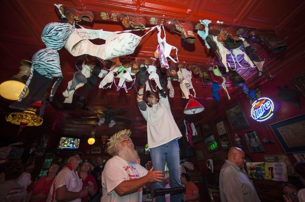 A patron of the Holler House bar participates in the Great Bra Rehanging event in Milwaukee, Wisconsin June 14, 2013. A Milwaukee city inspector had in April ordered Holler House's owner Marcy Skowronski to take down the bras, which have been hanging in the bar for the last 45 years as tradition, saying they were a fire hazard, but has since backed out of the order.