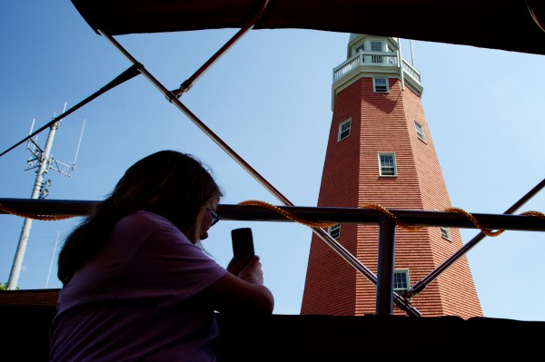 A woman snaps a picture of Portland's observatory atop Munjoy Hill Friday while on a guided tour atop a 1971 fire truck. The Portland Fire Engine Co. offers tours of the city daily.