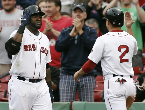 Boston Red Sox player David Ortiz (left) greets teammate Jacoby Ellsbury after Ellsbury scored on a triple by Shane Victorino during the sixth inning at Fenway Park in Boston in the first game of a doubleheader Tuesday.