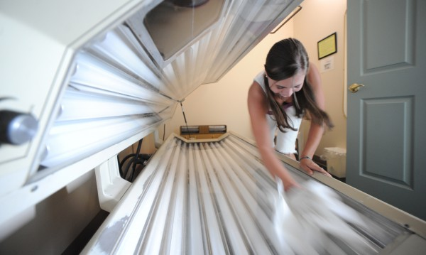 Tanning technician Meghan Jordan wipes down a tanning bed after a client has left Sunrich Tanning Boutique in Bangor on July 29, 2009.