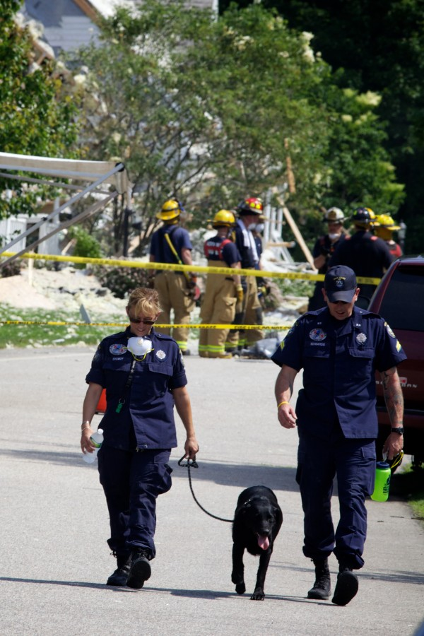 Safety personnel and a police canine leave the scene of an explosion on Gables Drive in Yarmouth Tuesday morning.