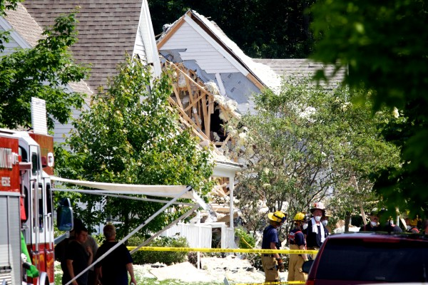 Firefighters stand near an exploded house on Gables Drive in Yarmouth Tuesday morning.
